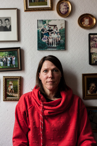 Portrait of Christine, a teacher, in front of her family pictures