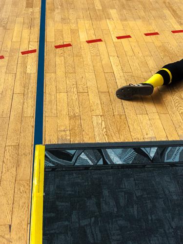 Der Unterschenkel eines Spielers beim Blindensport Torball liegt auf dem Hallenboden vor einem Markierungs-Teppich