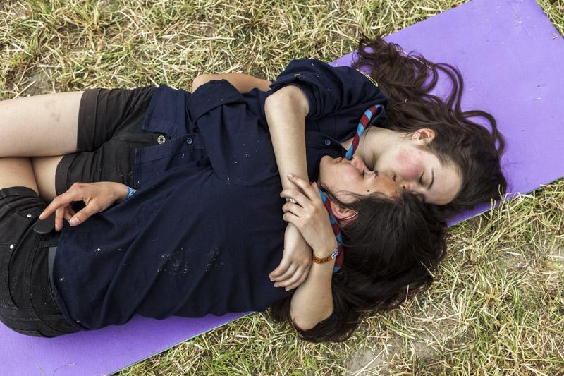 Zwei Junge Pfadfinderinnen liegen im Gras auf einer Isomatte und umarmen sich. / Two girl scouts lie in the grass and hug each other.