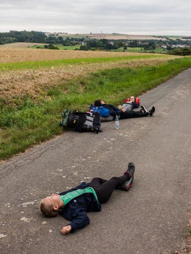 Junge Pfadfinderinnen machen eine Pause während einer Wanderung und liegen auf einem Feldweg bei Immenhausen. / Young female scouts take a break during a hike and lie on a field path near Immenhausen.