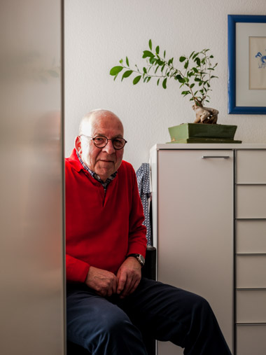 A portrait of Stephan an industrial consultant sitting in his bedroom.