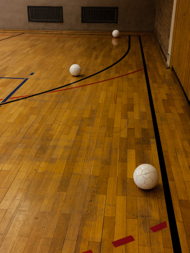 Spezielle Bälle, in denen eine Rassel eingebaut ist, liegen während des Torball-Traings auf dem Hallendboden verteilt.