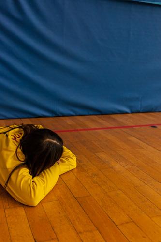 Ein Spielerin liegt während einer Trainigspause auf dem dem Hallenboden und ruht sich aus.