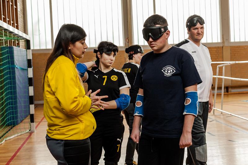 Spieler des Blindensports Torball tragen Dunkelbrillen während sie auf den Beginn des Trainings warten
