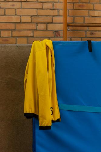 Eine gelbe Trainingsjacke des BVB hängt an einem an die Wand gelehnten Weichboden.