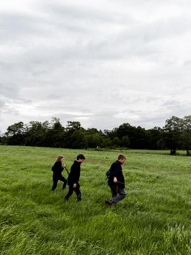 Drei junge Pfadfinder*innen laufen währende eines Geländepsiels über eine Wiese bei Bremen / Three young Scouts walk over a meadow near Bremen during an terrain game.
