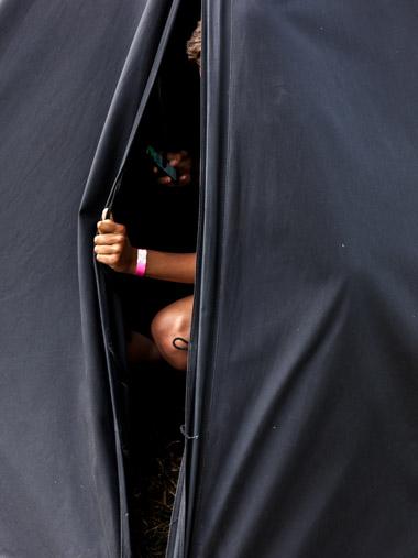 Ein Pfadfinder wirft im Zelt einen Blick auf sein Smartphone. / A boy scout takes a look at his smartphone in the tent.