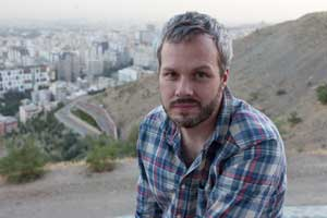 Portrait of photographer Stephan Lucka in front of Tehran´s skyline