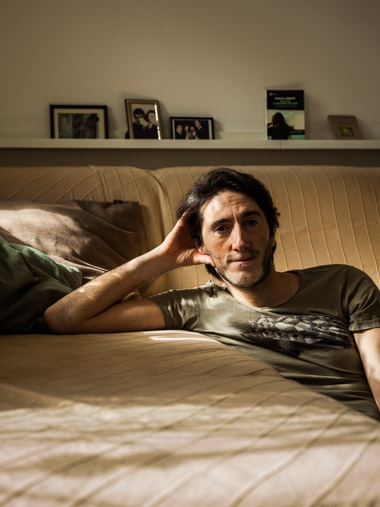 Portrait of biologist Stefano sitting next to his sofa in his living room.