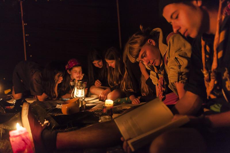 """Sheyma, Mira (Pfadfindername:""""Leia""""), Miray, Jolina (Pfadfindername:""""Luri""""), Lisa (Pfadfindername:""""Punkki"""") und Rafael (Pfadfindername:""""Tarzan"""", von links) schauen während einer Singerunde in der """"Jurte"""" im Schein des Lagerfeuers in Liederbücher. / Sheyma , Mira (scout name: """"Leia""""), Miray, Jolina (scout name: """"Luri""""), Lisa (scout name: """"Punkki"""") and Rafael (scout name: """"Tarzan"""", from left) are looking at song books during a singing round in the """"yurt"""" in the light of the campfire."""