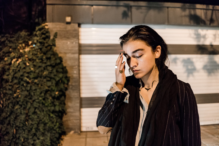 Iranian female singer Meshkat standing on the street at night, contemplating.