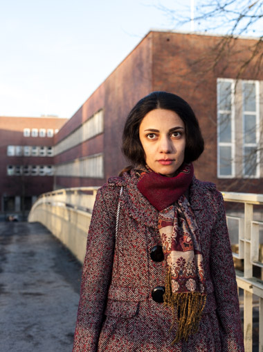 A portrait of Mina, a photographer from Iran, standing in front of the university.
