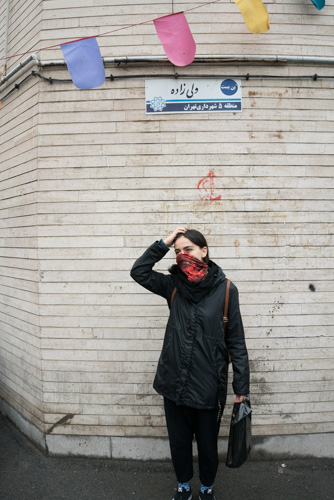 Iranian singer Meshkat hiding behind her scarf and holding her head in a public alley.